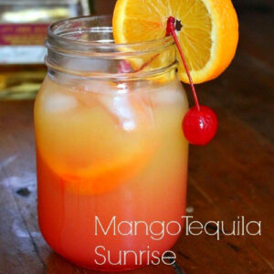 Closeup of a mango tequila sunrise garnished with an orange and a cherry.