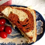 A sandwich made with a light bread with a dark red swirl.