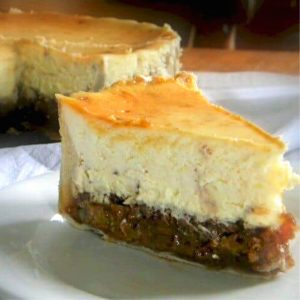 slice of pecan pie cheesecake in front of the whole cake.