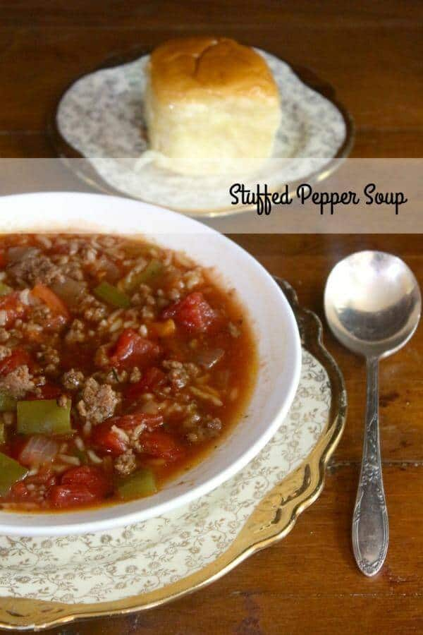 A blow of stuffed pepper soup with a dinner roll in the background.