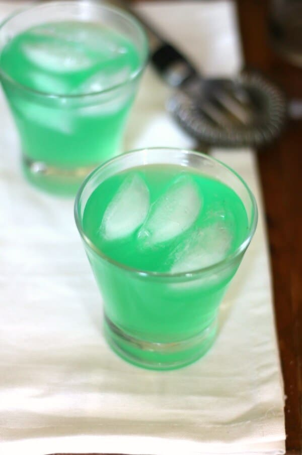 Overhead view of two green Hulk cocktails in glasses.