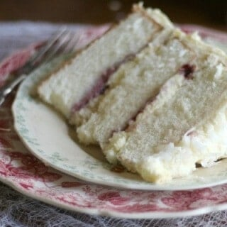 This Southern Coconut cake is three layers of amazing! Raspberry filling, fluffy whipped white chocolate frosting. From RestlessChipotle.com