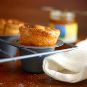 Closeup of golden cornmeal popovers in a popover pan with a white towel underneath.