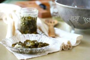 Candied jalapenos in a glass serving dish with the jar of them in the background.