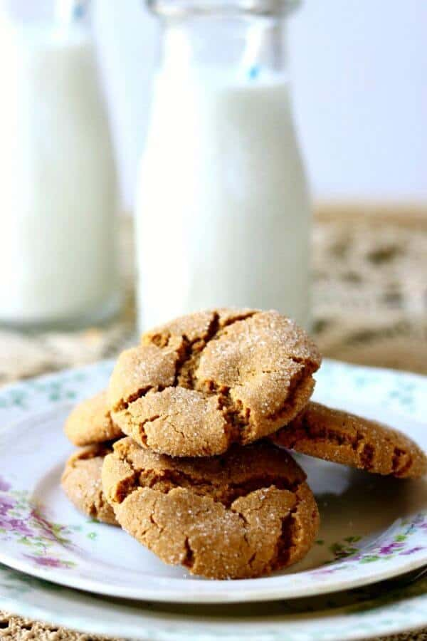 Plate of cookies with a bottle of milk in the background.