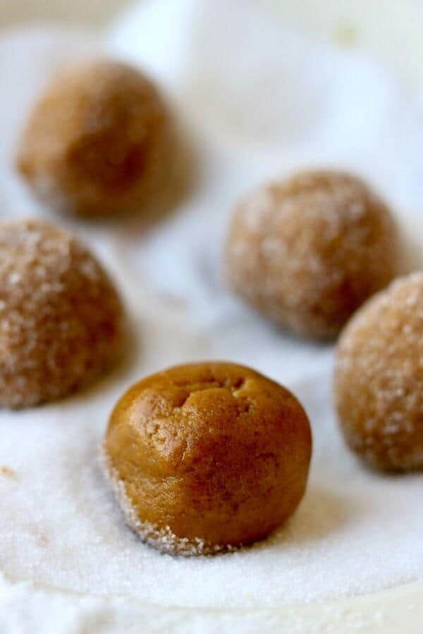 Balls of homemade peanut butter cookie dough being rolled in sugar.