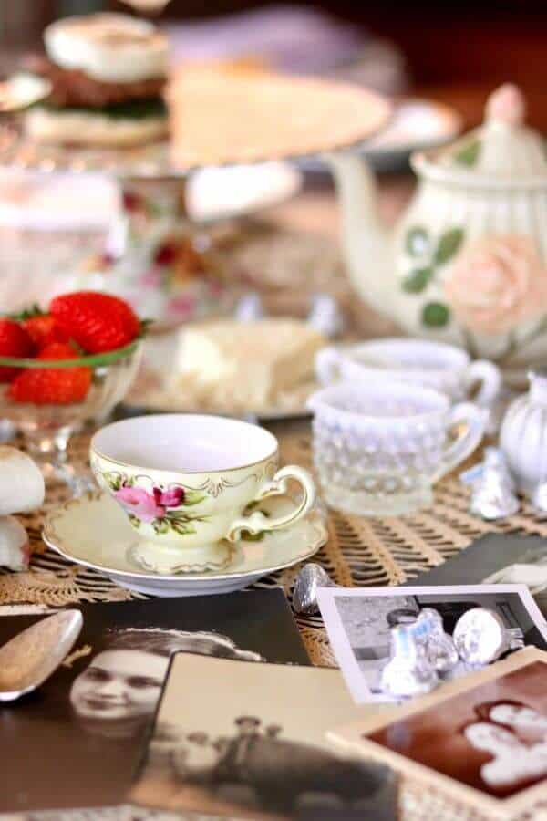A vintage table setting with closeup of a teacup. Old pictures of moms are on the table.