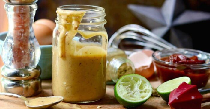 Chipotle aioli in a glass jar with ingredients surrounding it.