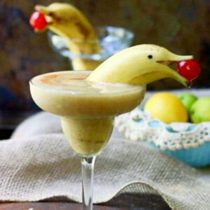 Closeup of two banana daiquiris garnished with bananas cut to look like dolphins.