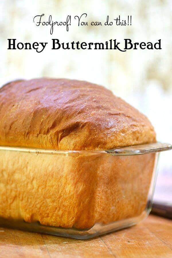 A loaf of honey buttermilk bread cooling in a glass baking dish.