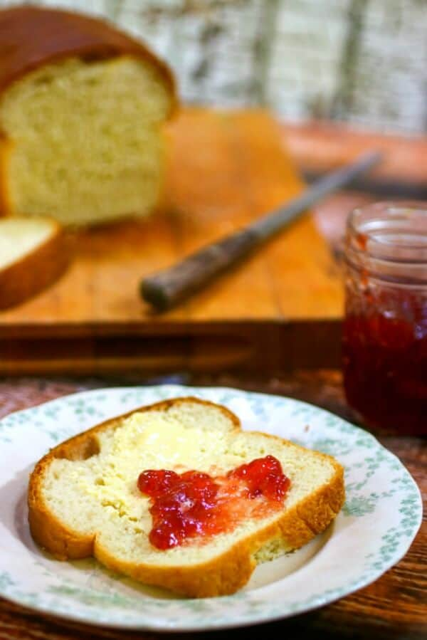 A slice of of homemade white bread spread with strawberry jam.