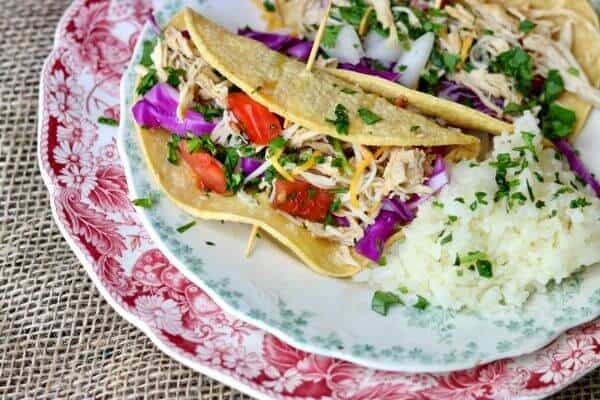 Family favorite! Slow cooker tequila lime chicken tacos is an easy Tex-Mex dinner recipe that cooks right in your crock pot all day long. Use chicken thighs or breast for a deliciously easy weeknight meal! Perfect for a weekend taco bar! From RestlessChipotle.com