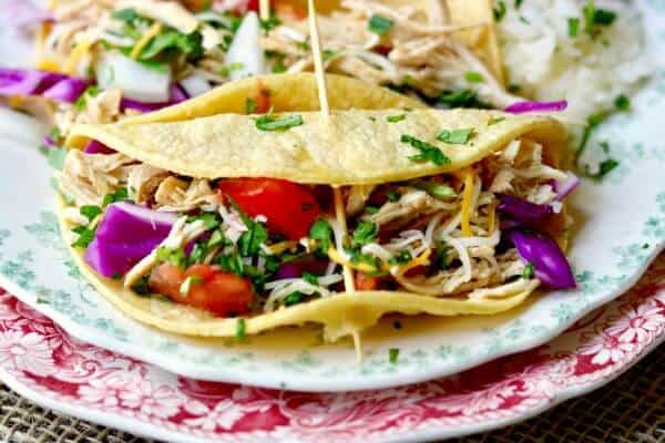 Easy! Slow cooker tequila lime chicken tacos is an easy Tex-Mex dinner recipe that cooks right in your crock pot all day long. Use chicken thighs or breast for a deliciously easy weeknight meal! Perfect for a weekend taco bar! From RestlessChipotle.com