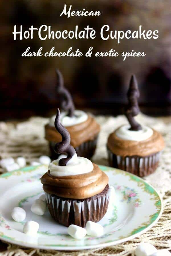 Three Mexican hot chocolate cupcakes covered in chocolate and marshmallow frosting with a dark chocolate garnish on top. Title image.