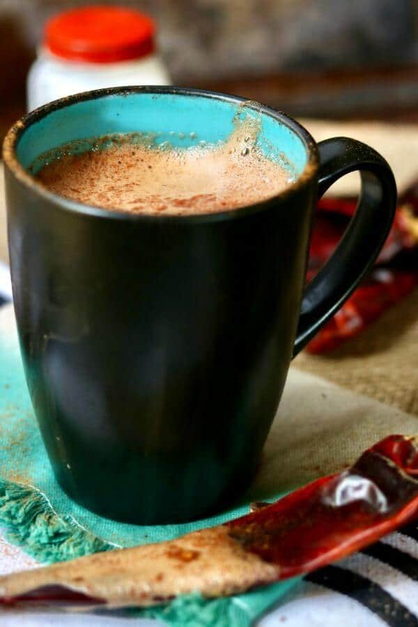 A black mug with a teal interior holds a frothy serving of Spiked Mexican Hot Chocolate.Guijillo chiles are at the base of the mug.