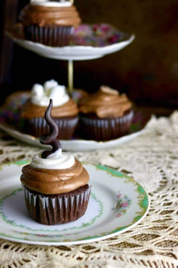 A close up of Mexican hot chocolate cupcakes on antique china with more cupcakes in the background.