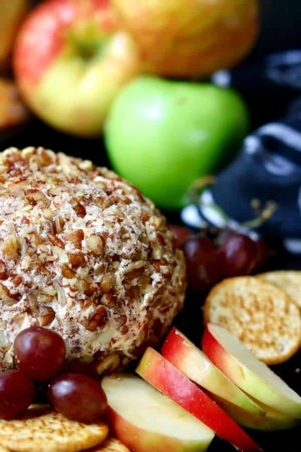 Close up of apple cheddar cheese ball with chopped pecans pressed into it to cover. Sliced apples to the side.