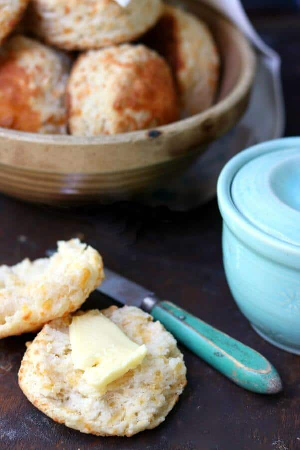 A cheddar cheese biscuit is cut in half and spread with butter. A green handled knife is next to the biscuit and a yellow ware bowl filled with biscuits is in the background