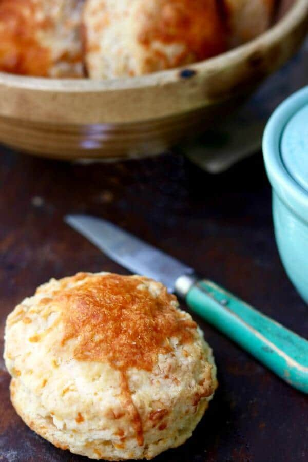 A whole cheddar cheese biscuit with an old green handled knife beside it, sitting next to a yellow ware bowl of biscuits.