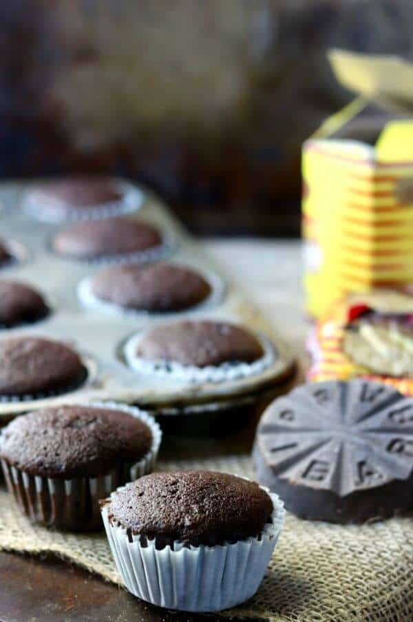 Unfrosted Mexican hot chocolate cupcakes next to a disk of Mexican chocolate.