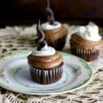 Square image of three Mexican hot chocolate cupcakes on a lace tablecloth