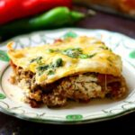 Spicy meat and gooey cheese ooze out of a cut piece of the easy mexican lasagna recipe topped with cilantro.