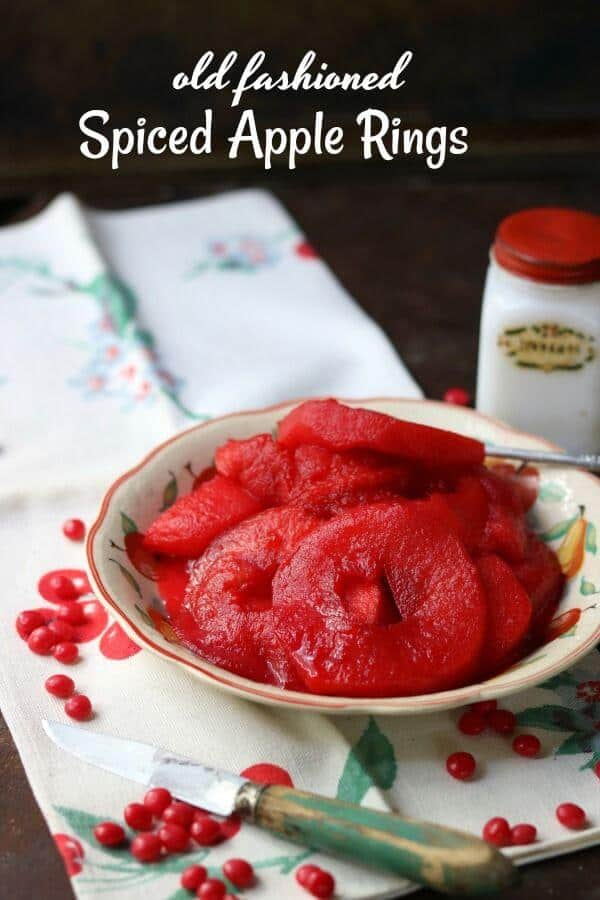 Bright red spiced apple rings made with Red Hots candy are placed in a bowl on a napkin