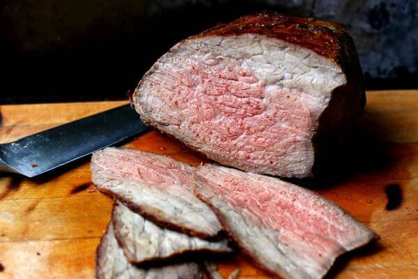 Sliced beef round roast on cutting board - feature image