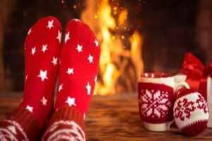 a person's feet in red socks with white stars in front of a fireplace. A cup of coffee is to the side. Feature image for best gifts for coffee lovers
