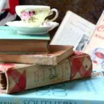 Feature image for best gifts for cookbook collectors. Stack of antique cookbooks with a vintage teacup and saucer on the top. Teacup has pink roses on it.