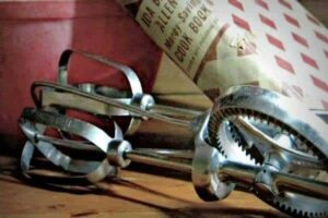 Antique dover beater lies next to a red mixing bowl with an old cookbook leaning on it.