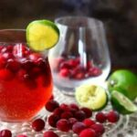 Cranberry Moscow Mule in a glass - an empty glass is in the background. Cranberries are at the base of the glasses.
