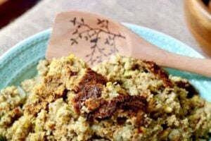 Close up of Southern cornbread dressing is in a turquoise bowl with a wooden spoon in it ready to serve the family.