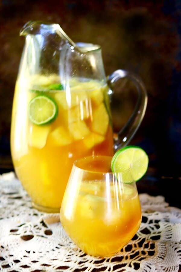 A glass pitcher of tropical pineapple sangria is behind a glass of sangria garnished with a lime.