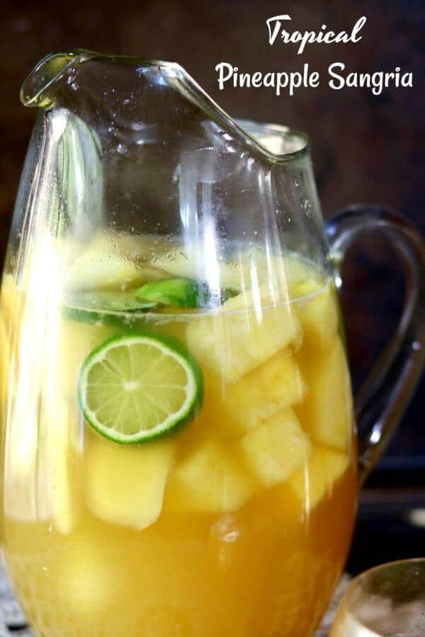 Closeup of a glass pitcher filled with yellow tropical pineapple sangria. Sliced of lime and bits of pineapple float in the pitcher.