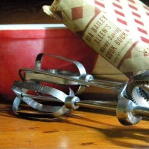 antique egg beater, cookbook and red mixing bowl on a wooden counter.