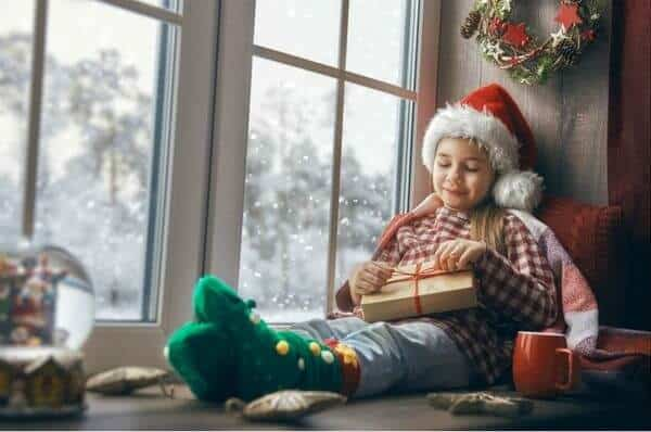 Little girl in a santa hat sitting on a window seat with gifts - best gifts for chocolate lovers feature image