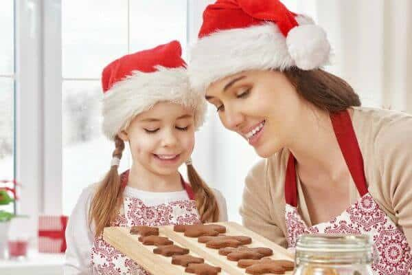 woman and child wearing red santa claus hats looking at a tray of cookies - feature image best gifts for the gourmet