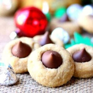 peanut butter blossom cookie with hershey's kisses in silver wrappers - peanut butter blossoms recipe image