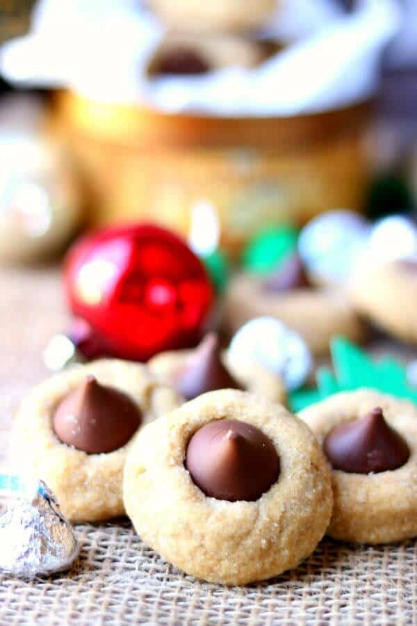 close up of peanut butter kiss cookies with christmas ornaments in the background. Peanut butter blossoms recipe image2