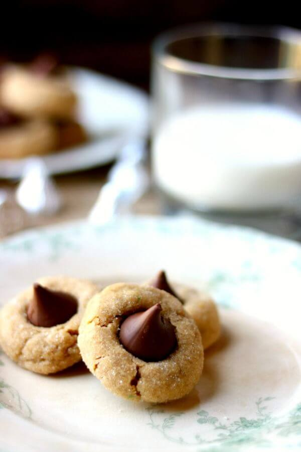peanut butter blossoms cookies on a vintage green and white plate with a glass of milk in the background - peanut butter blossoms recipe image with milk