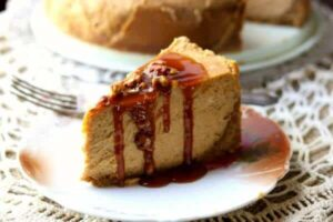 pumpkin cheesecake with gingersnap crust is sliced and covered with caramel sauce and pecans. Feature image