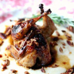 A whole, roasted quail on a bed of cheese grits.