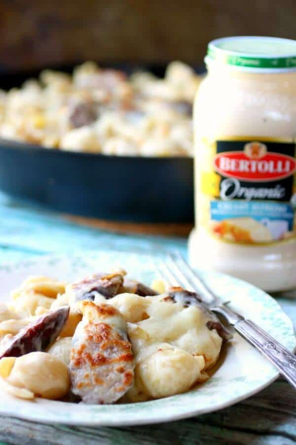 closeup of sausage alfredo with a jar of Bertolli Organic Alfredo sauce in the background.