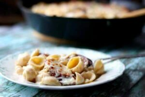 Sausage Alfredo on a vintage plate with skillet in the background - feature image