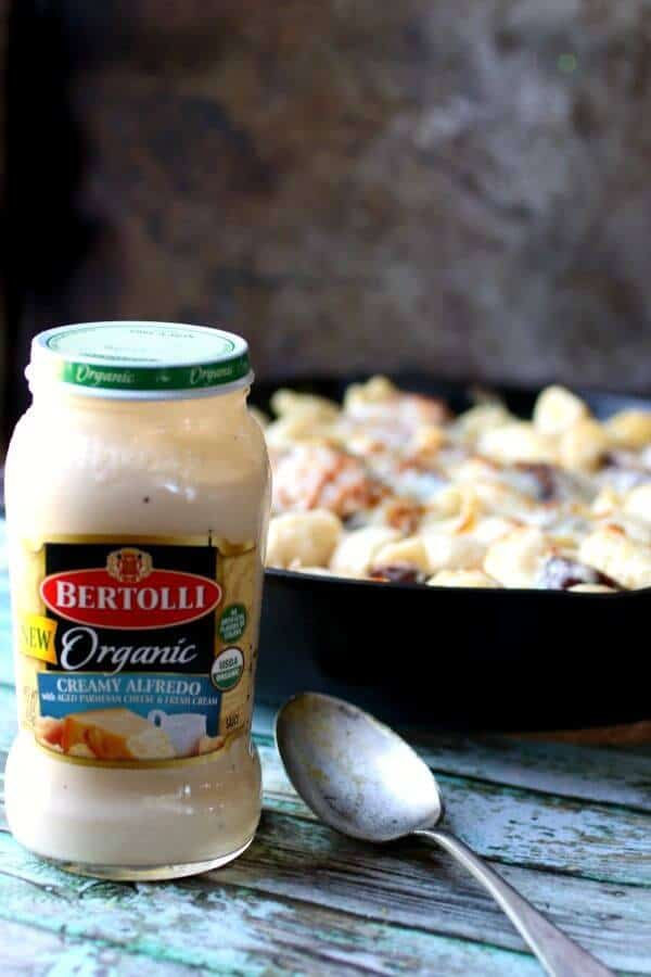 Jar of Bertolli organic Alfredo sauce in the foreground with a spoon - sausage alfredo in a skillet in the background
