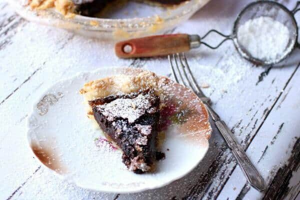 A horizontal image of chocolate chess pie with a silver fork next to it. Feature image.