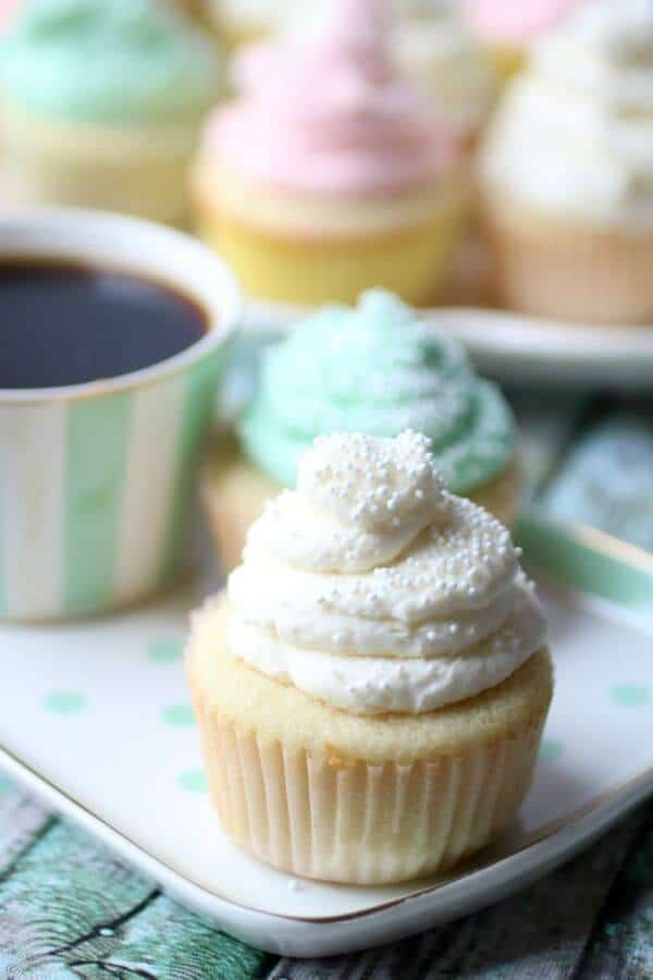 Homemade white cupcake with a creamy white frosting on a pastel green plate