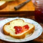 Slice of homemade bread with strawberry jam on it.