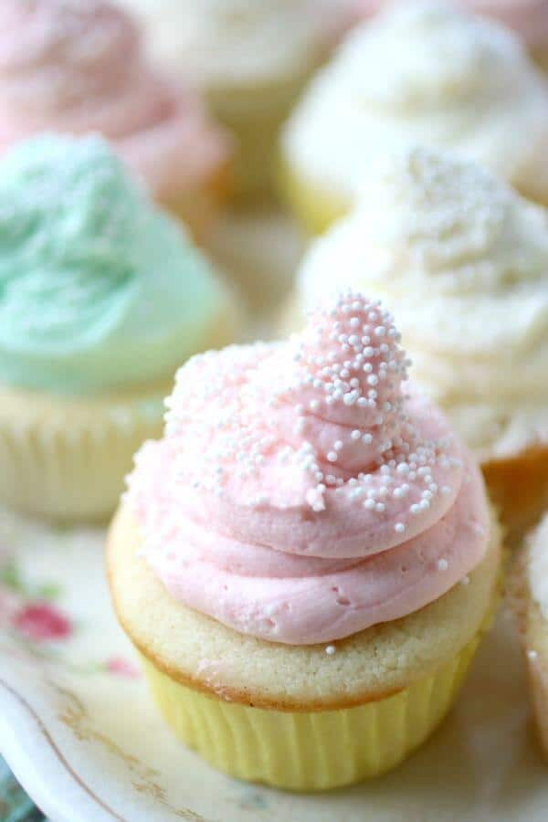 A tall cloud of whipped cream cheese frosting is piped on the top of the homemade white cupcakes recipe cupcake.